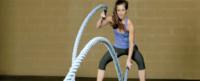 Female athlete swinging rope during training.
