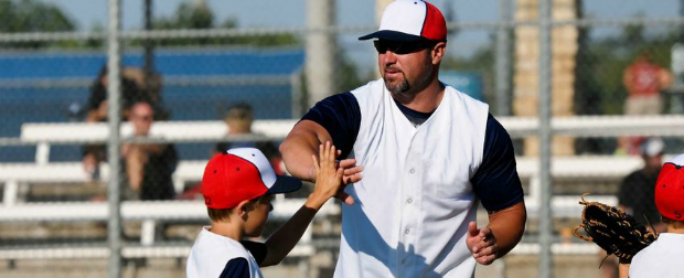 Sports coach high-fiving young baseball player after game.