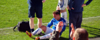 Soccer athlete sitting on the field after pulling his hamstring.