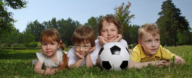 Picture of young children in the grass with a soccer ball