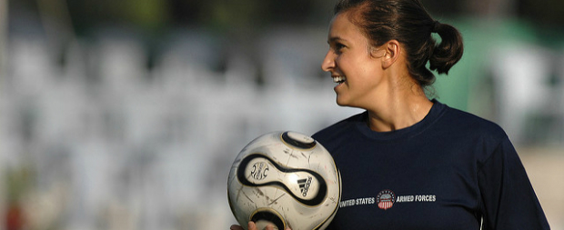 Young female athlete holding soccer ball.