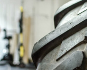 Male trainer working out with a tire.