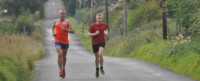 Two athletes running up hill to increase speed.
