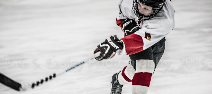 Young hockey player taking a shot on goal