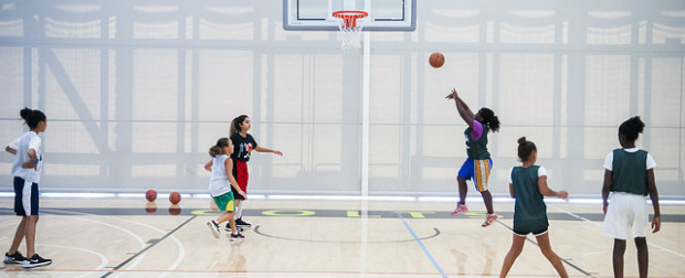 Athletes playing basketball on court.