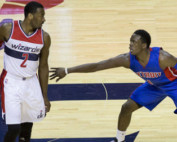 Two athletes playing basketball against one another.