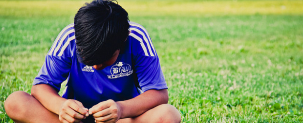 Youth athlete sitting on soccer field.