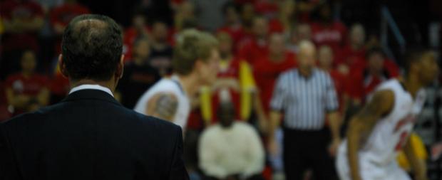 Sports coaching training athletes on basketball court.