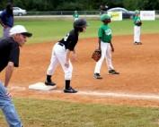 Coach guarding third base during baseball game.