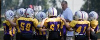 Coach helping young athletes understand football.